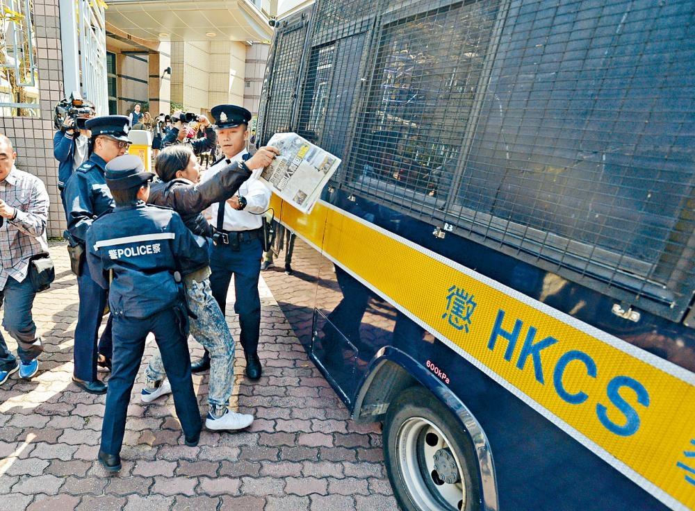 「女長毛」在庭外欲衝向囚車時被警員阻止。