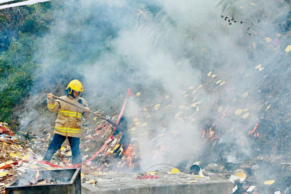 疑路祭遺下火種引致山火,消防員用山火拍撲救。