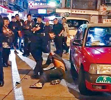南亞漢強行竄入的士車底,警員將他拉出。