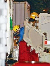 消防員從貨櫃內檢走一罐白電油。