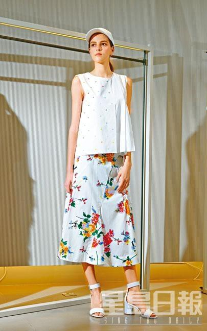 白色小波點圖案百褶剪裁背心、彩色印花圖案白色半截裙、白色Cap帽、白色高跟涼鞋。