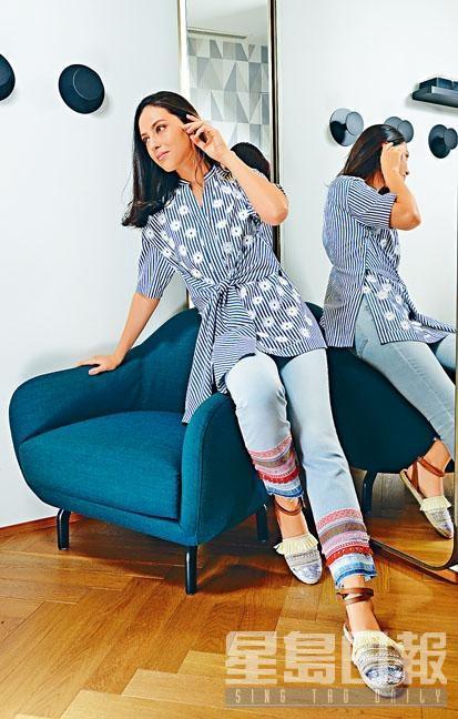 藍白色印花拼條子圖案束腰上衣、褲腳綴民族飾帶的淺藍色牛仔褲、綴流穗銀色尖頭平底鞋。