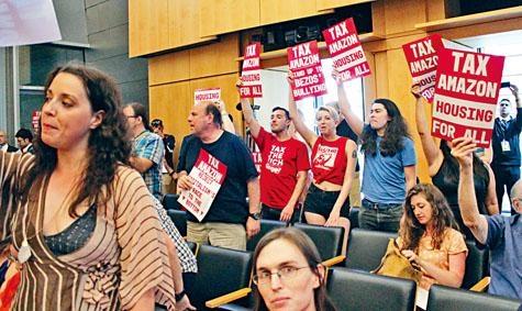 西雅圖支持和反對人頭稅的民眾,帶同標語牌出席市議會上周舉行的諮詢會。