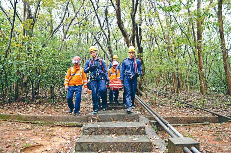 救援人員冒雨抬着墮坡受傷女子落山。