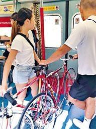 單車男女推着單車乘港鐵列車。