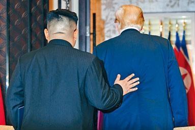 兩人簽署聯合聲明後,一起離開時金正恩輕拍特朗普背部。