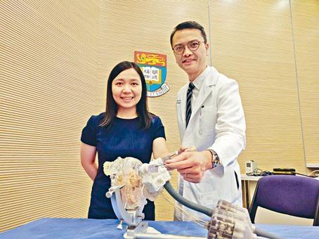 港大機械工程系博士研究生郭子彥與中大外科學系神經外科醫生陳達明,示範在機械人系統定位後,人手插入電極針的步驟。