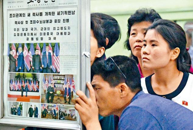 北韓民眾昨天在平壤一個地鐵站的報告板,觀看《勞動新聞》的美朝峰會報道。