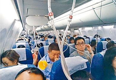 空中服務員指示乘客戴上氧氣面罩。
