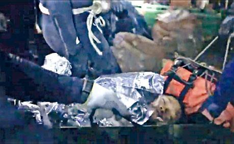 救援人員照料擔架上的孩子。