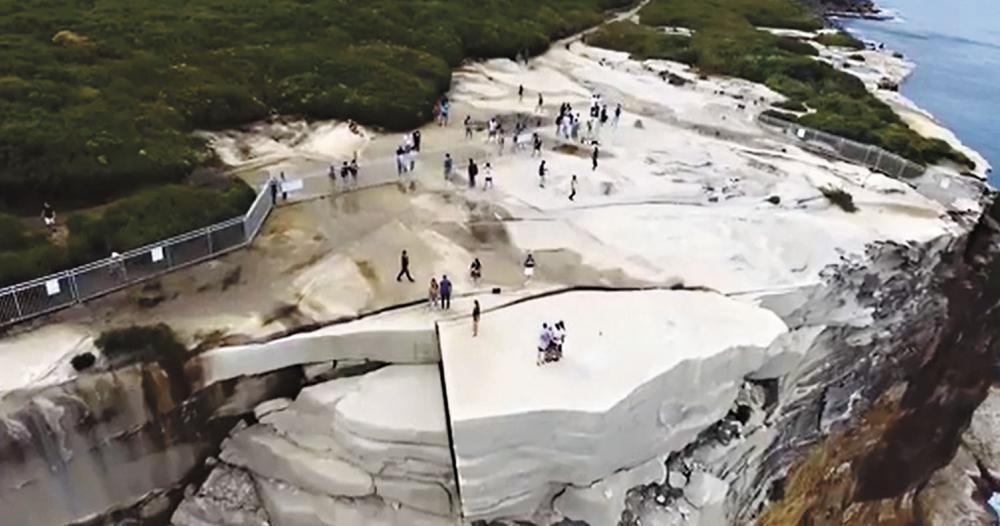 遊客無視警告,在結婚蛋糕岩上拍照。新聞公司