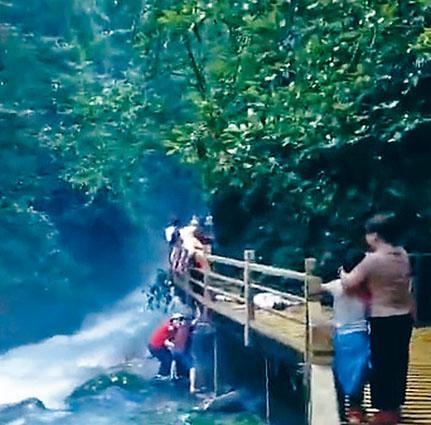 有遊客掉落河道,被合力拉回步道。