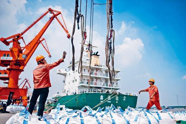 江蘇張家港市碼頭,工人正在裝卸一袋袋化學品。