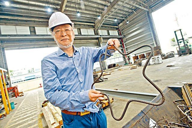 ■香港建築業物料聯會行政總裁甯漢崇,展示一個星形的鋼筋預製組件。