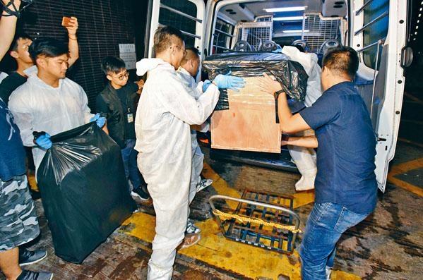 警員在張祺忠的辦公室搬走用作藏屍的旅行篋及木箱。