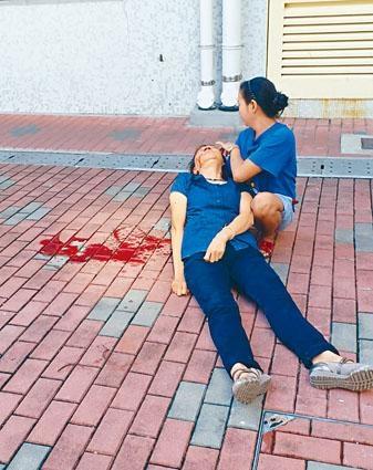 女住客遭墮下石屎擊中,頭部鮮血直流,由外傭緊抱待救。