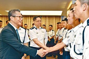 ■警務處處長盧偉聰(左二)及財政司司長陳茂波(左一)恭賀剛結業的見習督察。