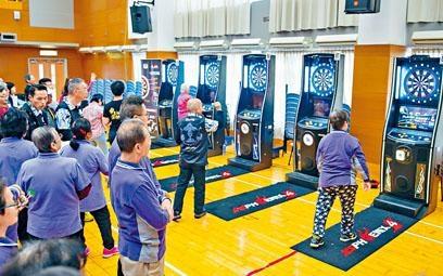 有機構教長者潮玩電子飛鏢及地壺球,改善長者集中力及平衡力。