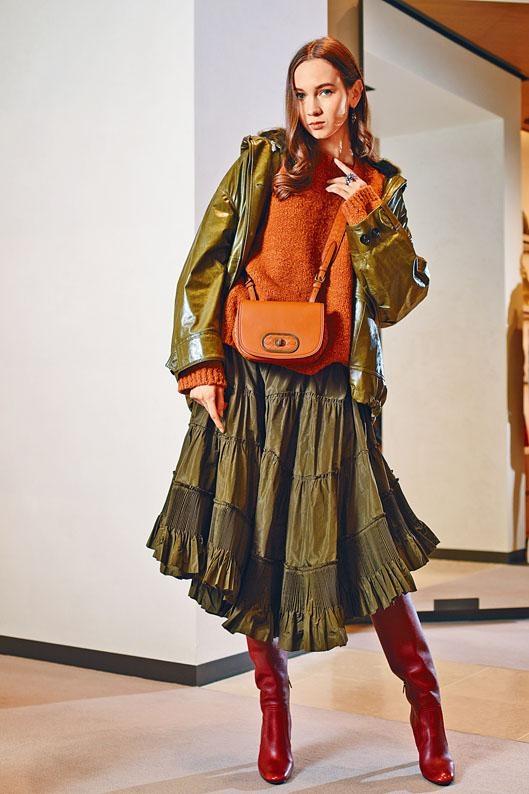 墨綠色羊皮皮褸、橙色Alpaca羊毛冷衫、墨綠色絲質半截裙、橙色羊皮BV Luna手袋、深玫瑰紅色牛皮長靴、耳環、指環。