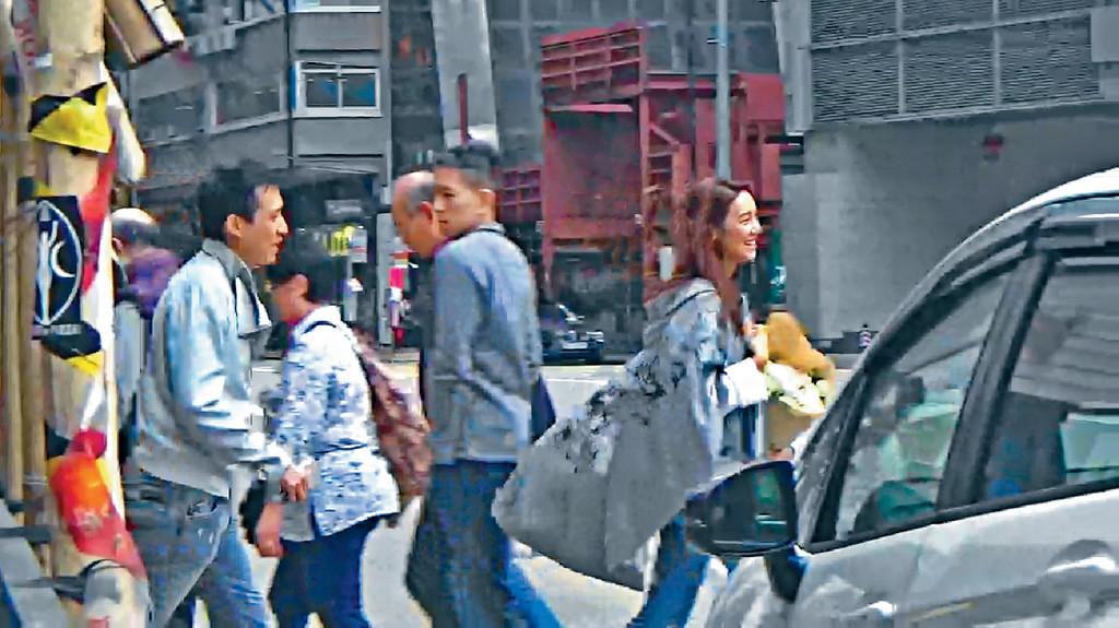 ■手執鮮花嘅Elva同男友前後腳行去取車時,笑得勁開心。