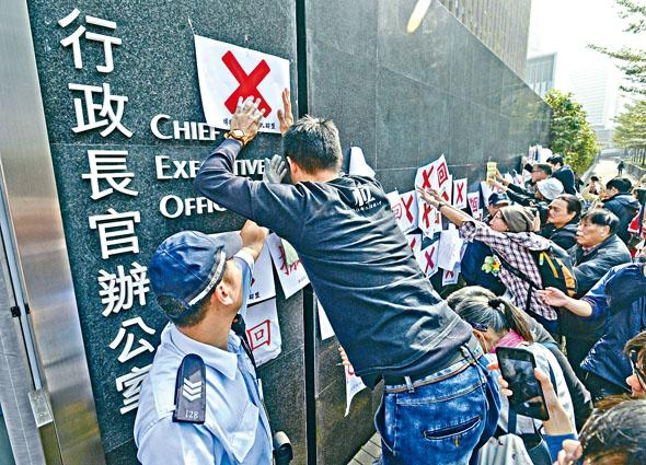 ■政府把長者綜援申請年齡上調至六十五歲,社會反對聲不絕。圖為團體在特首辦外張貼反對標語。