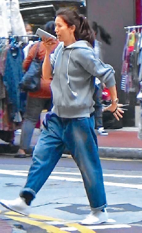 ■靚靚一邊錄語音訊息一邊過馬路。