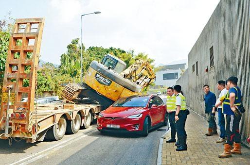 運送中的挖泥車墜下,壓向旁邊電能私家車。