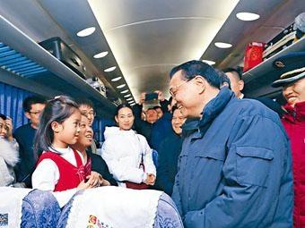 ■李克強在綠皮列車內和旅客交談。