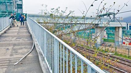 港鐵職員將被拆下的扶手,放回行人天橋斜路待查。