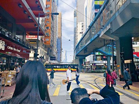 坤哥走到電車路上,拍攝演唱會海報。