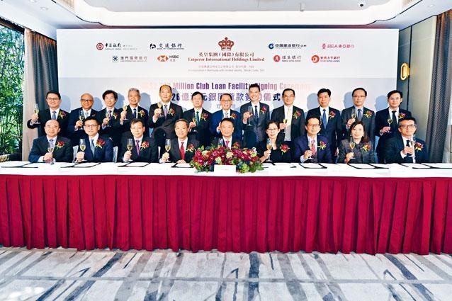 在英皇集團主席楊受成(上排左七)及其他銀行管理層見證下,英皇集團董事總經理黃志輝(下排左五)與八家銀行代表,包括中國銀行澳門分行、中國建設銀行(亞洲)、交通銀行香港分行、東亞銀行、澳門國際銀行、滙豐銀行、恒生銀行及華僑永亨銀行的代表,一同簽署銀團貸款協議。