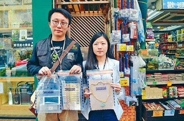女高級督察陳穎與同袍展示起回金頸鏈及現鈔等失物。