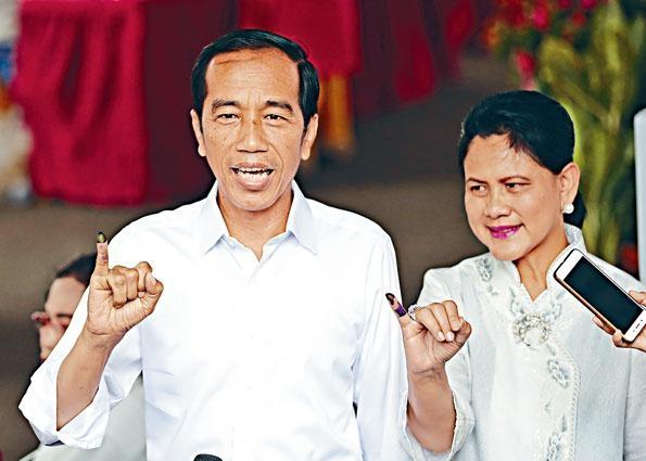 印尼總統維多多周三偕妻子在耶加達一個票站投票後,展示染墨水的手指。