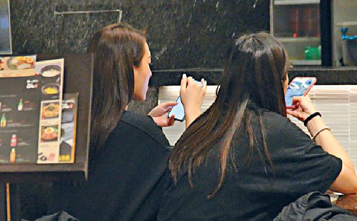 ■陳瀅邊食邊玩手機。