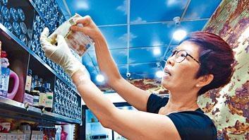 涼茶店職員檢視鈔票防偽特徵。