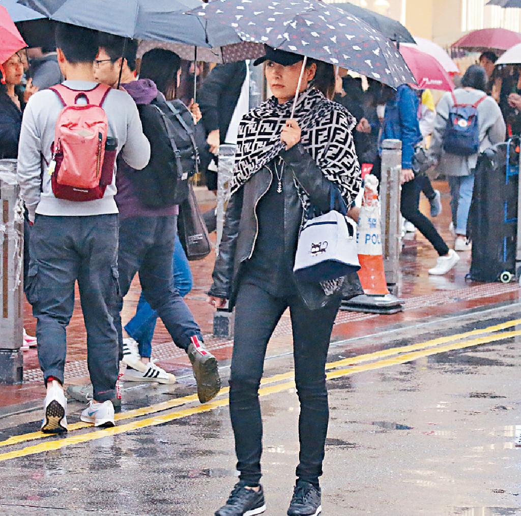 ■戴帽楊恭如撐傘行頭,由得母親死跟。