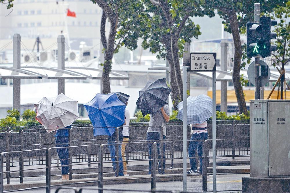 昨早天氣異常,市民「風雨同路」擋風擋雨情境如此一致。