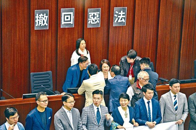 ■內務委員會會議會前,民主派議員走向主席台抗議,主席李慧琼獲黨友「護駕」。