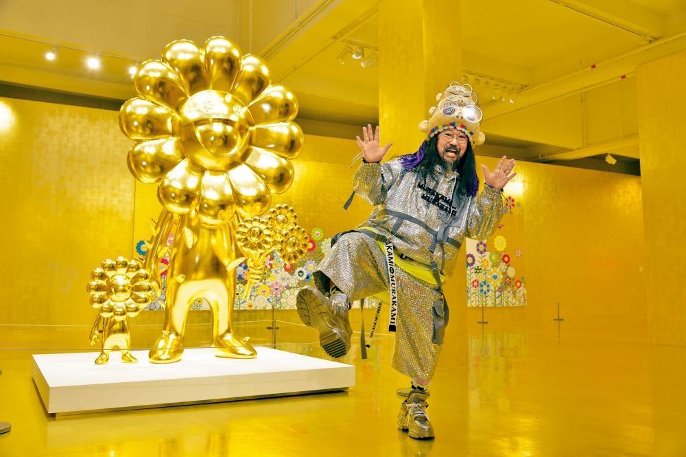 村上隆在染上一片金光的展廳「圓相」,舉腳拍照。