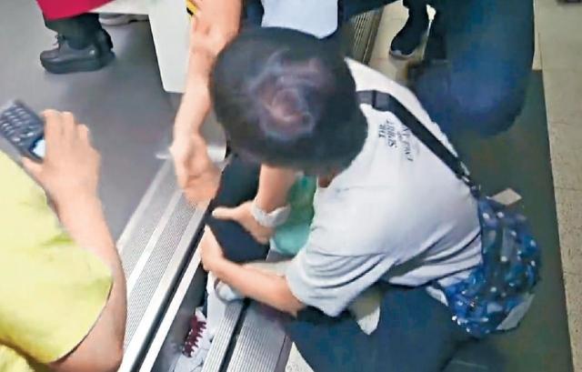 ■有人把腳放在車廂與月台之間的空隙,警員強行將之拉走。
