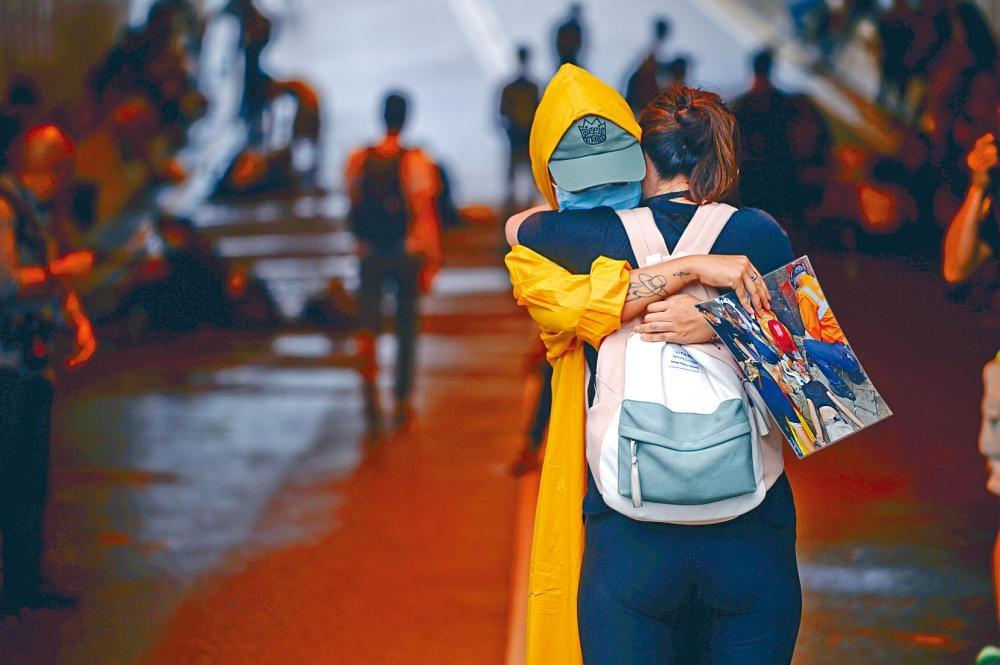 有示威者穿上黃色雨衣悼念死者,並與人相擁互相安慰。
