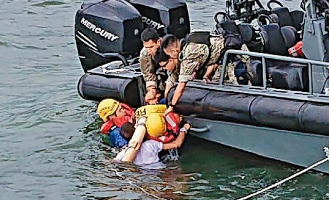 ■消防員跳落海,與休班警員合力將女事主救上小艇。