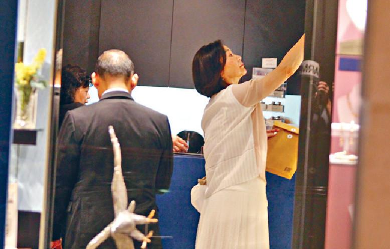 ■林青霞在店內伸手拿高處的相架來看。