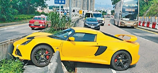 ■跑車撞向路中分隔石壆,半個車身直插花槽。