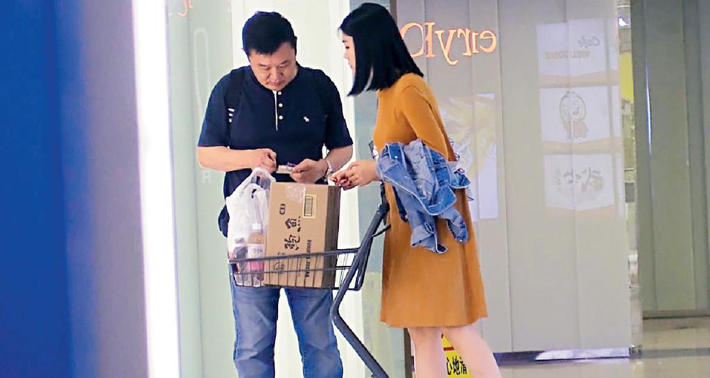 ■等(車立)時,程小東查看購物單據。