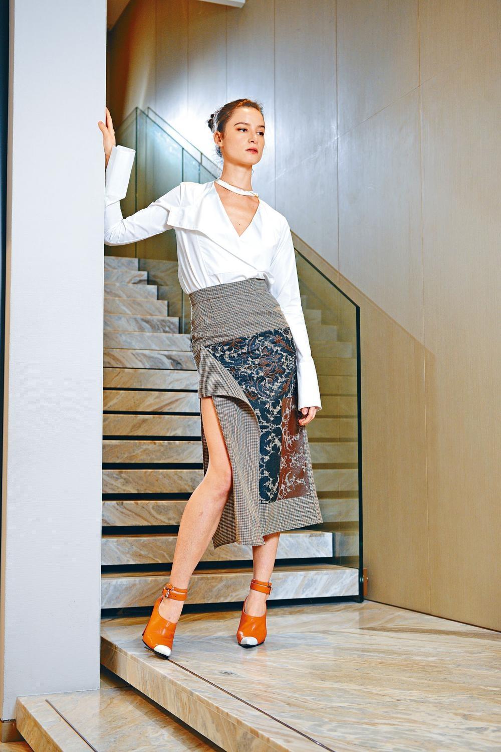 白色V領長袖恤衫,配襯格紋拼巴羅克式牆紙圖案半截裙,裙側採用開衩設計,帶來若隱若現的性感美態。
