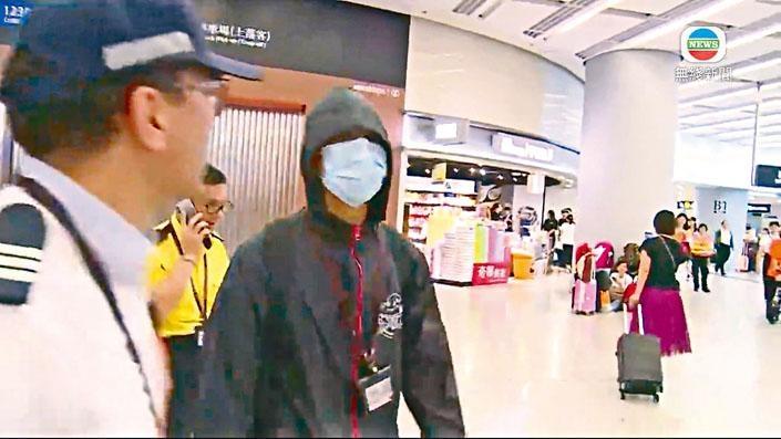 ■疑似港鐵員工(戴口罩)展示「香港撐住」海報後,被保安帶走。
