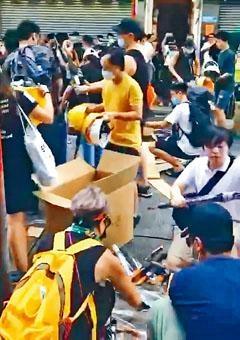 ■部分示威者有組織性,一個手勢搬來大批頭盔及雨傘。