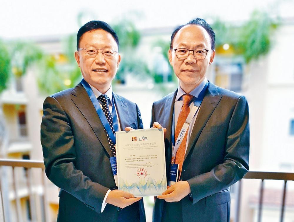 潘巍(左)從中美工程前沿論壇聯席主席暨中國工程院院士程京手上,接過「中國工程前沿傑出青年學者」榮譽證書。