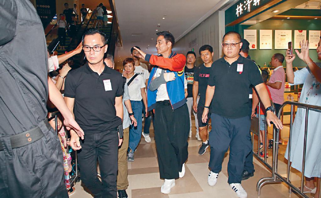 ■進入會場時,被保安包圍的華哥興奮地同Fans揮手及握手。
